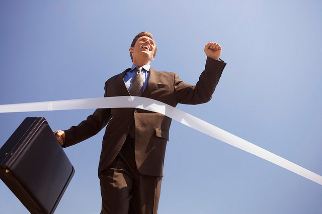 Businessman crossing the finish line by Meridican of Flickr